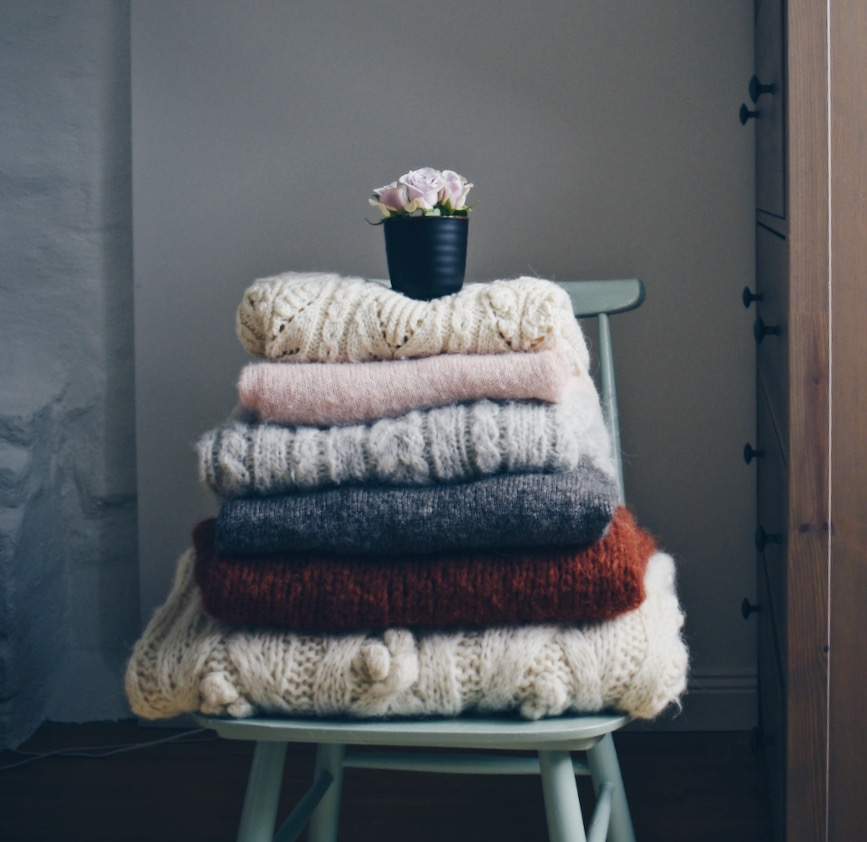 Things I'm excited about for Fall- Handmade pastel colored knitwear stacked up on a blue chair