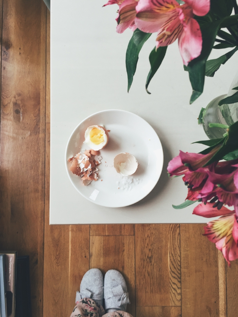 Eggs for breakfast on a white table with some flowers