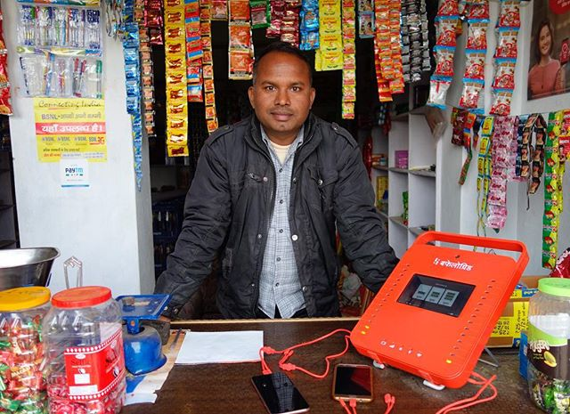 Say hello to Ramesh, one of the agents in our Airtel Pilot. This is his kirana store in the village of Mursan in Hathras in western Uttar Pradesh. His store, where he sells tobacco, sweets and toiletries in addition to Airtel balance and SIM cards, is in a small, new building on the outskirts of his village. He is proud of his store and the work he does for Airtel. While 4G connectivity is great in Mursan, the village stills lacks other basic infrastructure. Power lines have run into the village centre, but supply is unreliable and many homes and shops, including Mukesh's store, are still unconnected. But now he has a BuffaloGrid Hub, he can keep his phone and the phone's of people in his village charged throughout the day and well into the evening. We are proud to support Mukesh and his business through our work with Airtel.