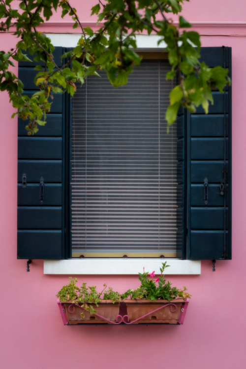 The shutters of this pink building invite the imagination, painting an idyllic image of one of Italy's most colorful towns.   Photo: Courtany Schick