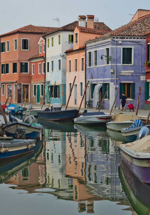 A local walks home past reflections of Burano in the water.   Photo: Courtany Schick