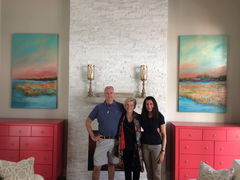 Cincinnati artist Trish Weeks celebrating a finished commissioned abstract landscape with clients.