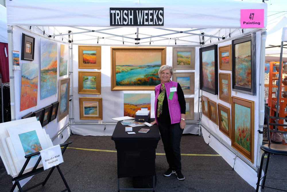 Artist Trish Weeks standing in her booth at the Hyde Park Art show surrounded by her colorful, abstract landscapes.