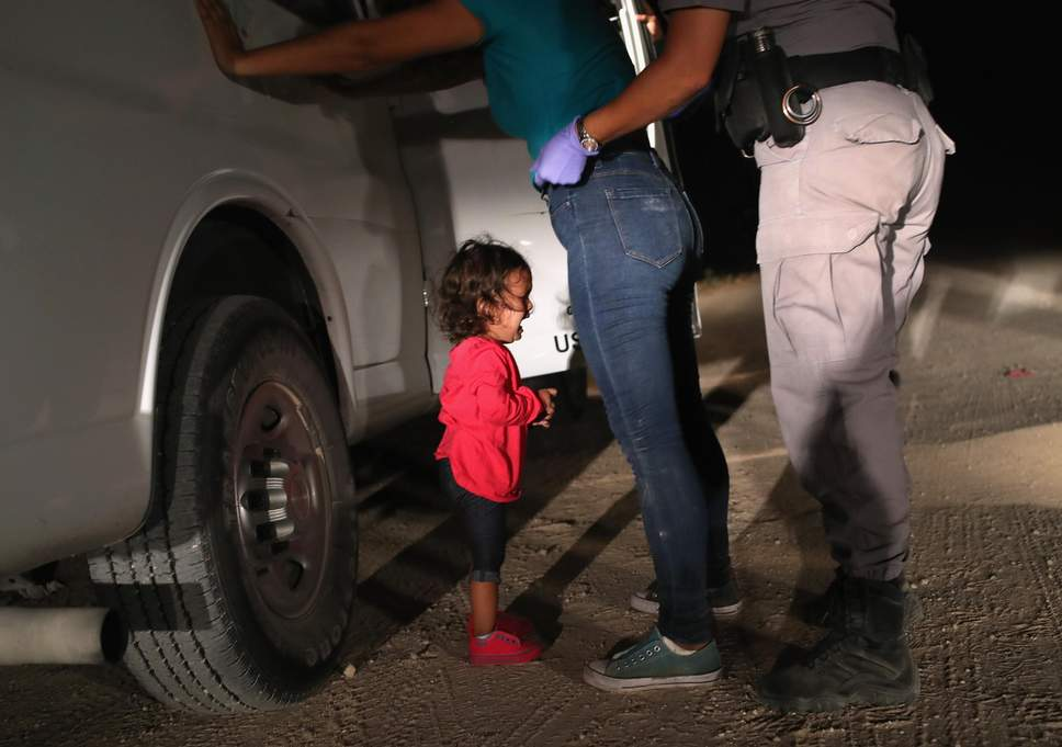 A two-year-old Honduran asylum seeker cries as her mother is searched and detained near the U.S.-Mexico border (John Moore/Getty Images)