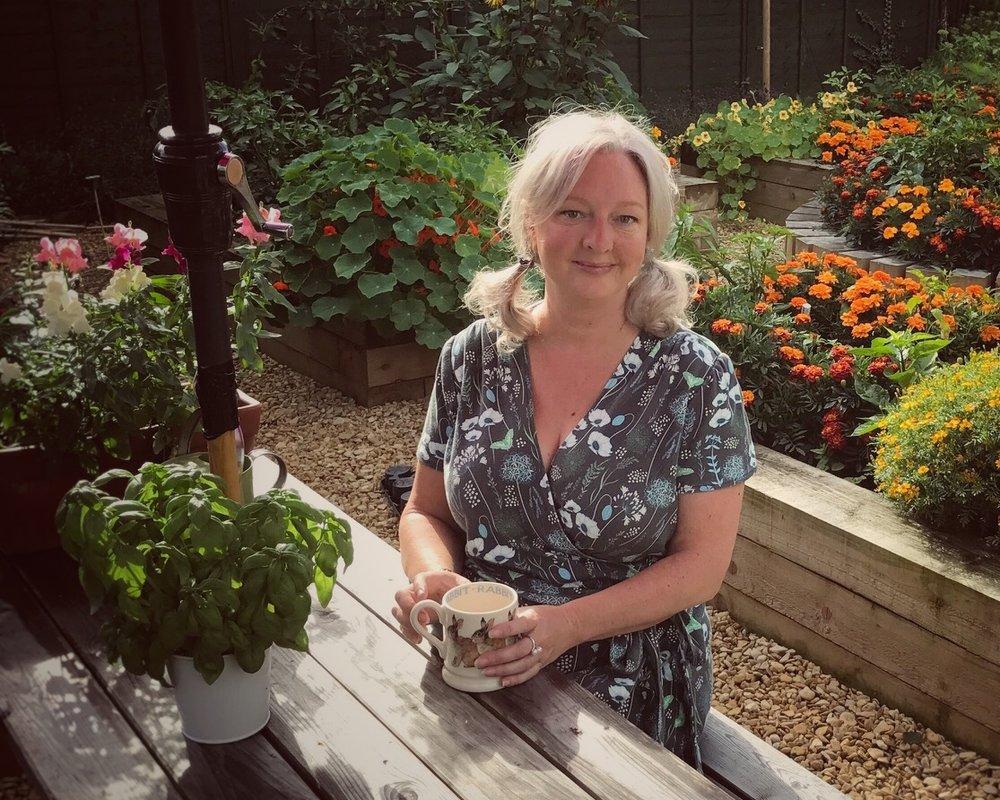 Photo of Jill enjoying a cup of tea in her garden
