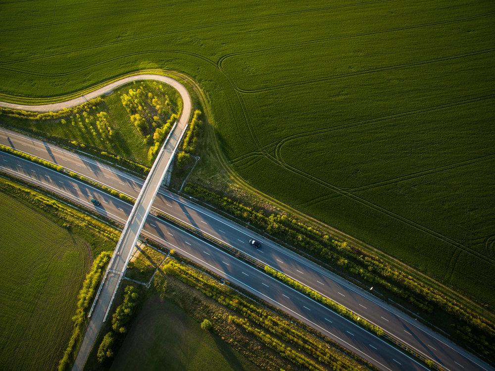 Aerialviewofahighwayamidfieldswithcarsonit(2).jpg