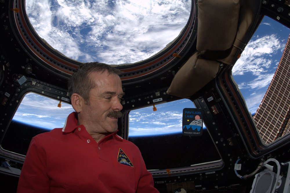 Col. Chris Hadfield and a floating PLRP badge in space