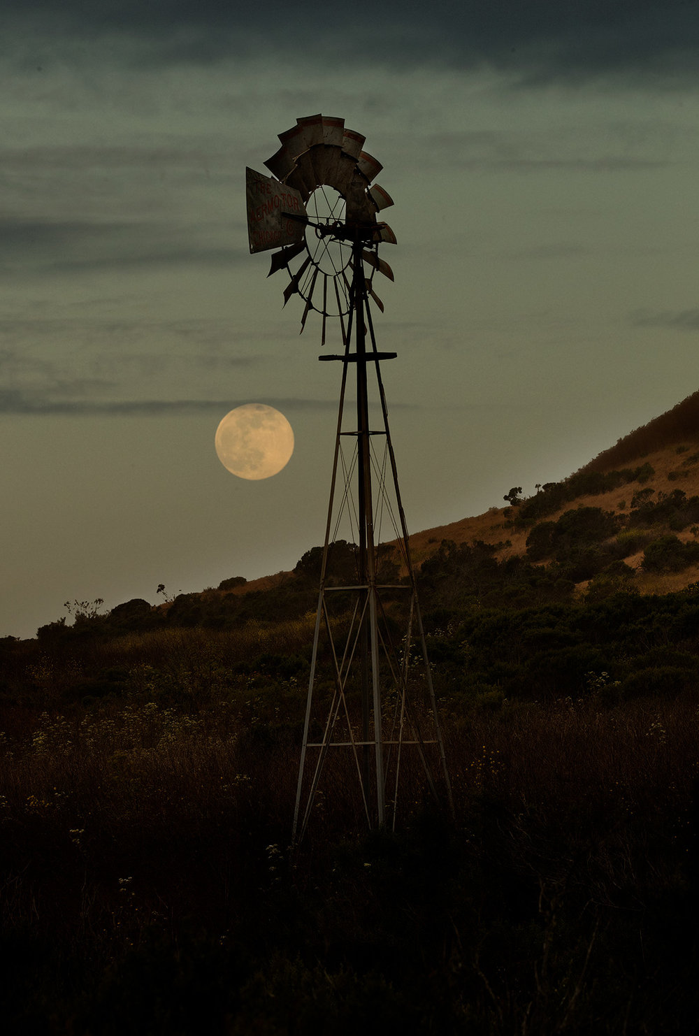 Moon rise and windmill. A delicate balance of light and dark is necessary to capture images like this, and the opportunity only presents itself one time a month.