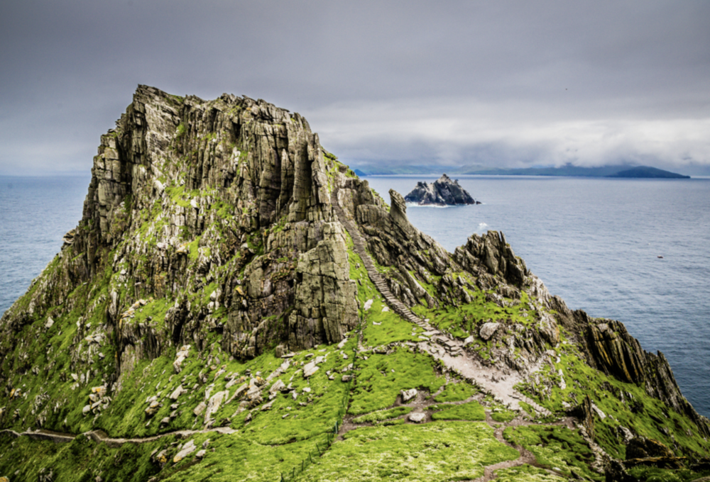 May 25:Skellig MichaelRing of KerrySkellig Ring - After breakfast, drive south on the Ring of Kerry to Portmagee. Take Skellig Ring to Portmagee where you will board a ferry to Skellig Michael. Sail on a grand adventure to the majestic Skellig Islands, which lie 7 miles off the west coast or Ireland.The first amazing sight is of the Small Skelligs and its snow covered-like appearance, when seen from a distance. Upon sailing closer you realize it is 75,000 nesting gannets that cover the Island. Onwards to Skellig Michael to marvel the monks, who built the monastery on this remote island 600ft above sea level.See locations where scenes from Episode VII and Episode VIII of the Star Wars franchise were shot. You will quickly see why this incredible location was such an attractive inclusion for the production team in the Star Wars universe.Skellig Michael also features birdlife in abundance - puffins, guillemots, kittiwakes to name a few all call these islands home throughout the year. You may also just encounter whales, dolphins, sunfish and even basking sharks roaming the surrounding waters.After you return to the mainland, set off to explore the Ring of Kerry. As you cruise along the Atlantic Coast on this spectacular mountain road through the towns of Kells, Derrynane, and Glenbeigh, you'll find a number of impressive sights, with various stopping points and photo opportunities. From Ross Castle and Muckross House to Torc Waterfall, Bog Village, and the glacial valley of the Gap of Dunloe, you'll want to keep your eyes peeled and your camera out.The ring also passes the golden beaches of Inch Beach, the Lakes of Killarney, the Macgillycuddy's Reeks mountains, Ladies View, and Dingle Bay looking out to the Dingle Peninsula.The coastal side of the loop offers a taste of the Wild Atlantic Way, and in County Kerry's Waterville, visitors tend to stop for photos with the waterfront Charlie Chaplin statue.Insider TipAs with many ring roads, there is little room to pass at some points. It's good to note that all tour buses travel counterclockwise from Killarney and that self-driving travelers can head clockwise for less traffic.At the bottom of the Ring of Kerry, you'll take a detour onto the lesser known, Skellig Ring. Skellig Ring is a predominantly coastal road that offers panoramic views of its namesake, the Skellig rocks. While it might be the Ring of Kerry's lesser sister, it certainly is far more impressive.From the highest point of the road you can climb the hill on the seaward side of the saddle in twenty minutes or so for the most magnificent views out to the Skellig Islands, across to the Dingle Peninsula and the Blaskets, and inland to the Iveragh Mountains.