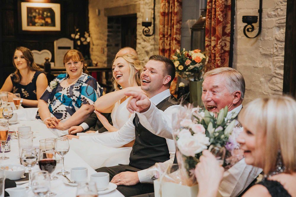 bride and groom laughing at their speeches at Holdsworth House