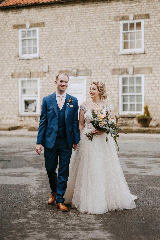 bride and groom walking through Helmsley