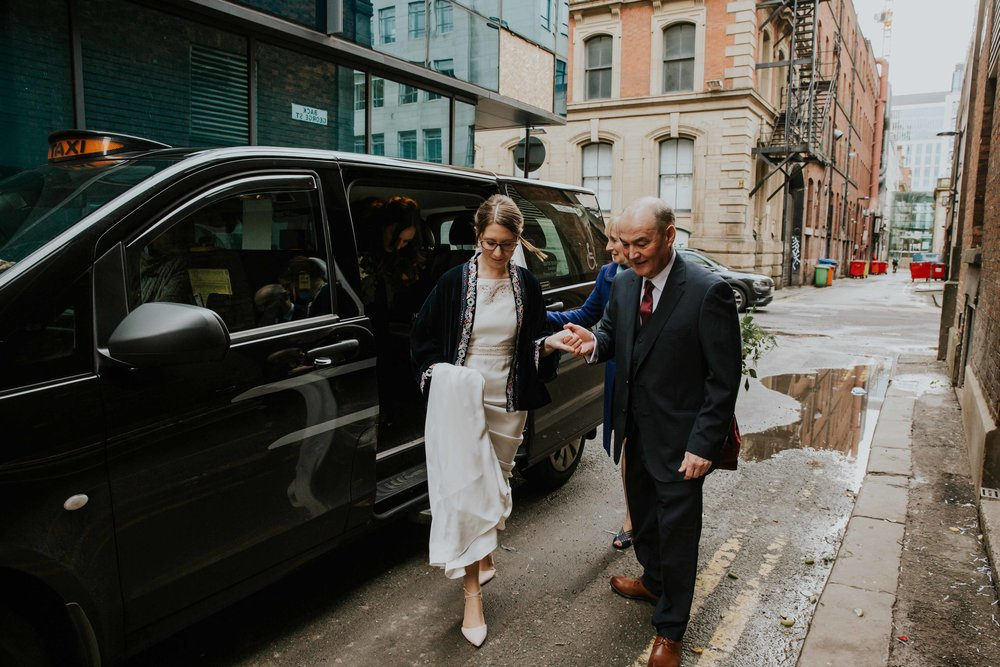 Bride getting out of wedding car at The Portico Library Manchester