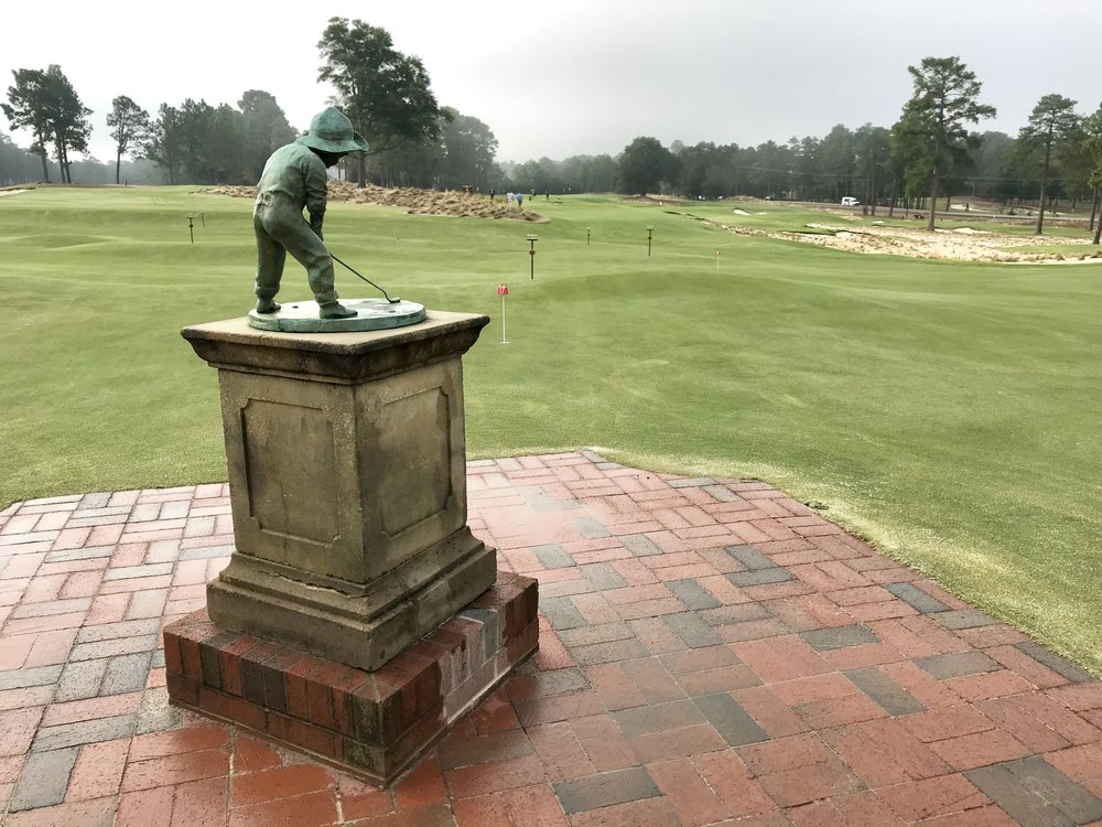 "The venerable ""Putter Boy"" statue stands in the the middle of a new 75,000 square foot practice green and ""Thistle Dhu"" putting course."