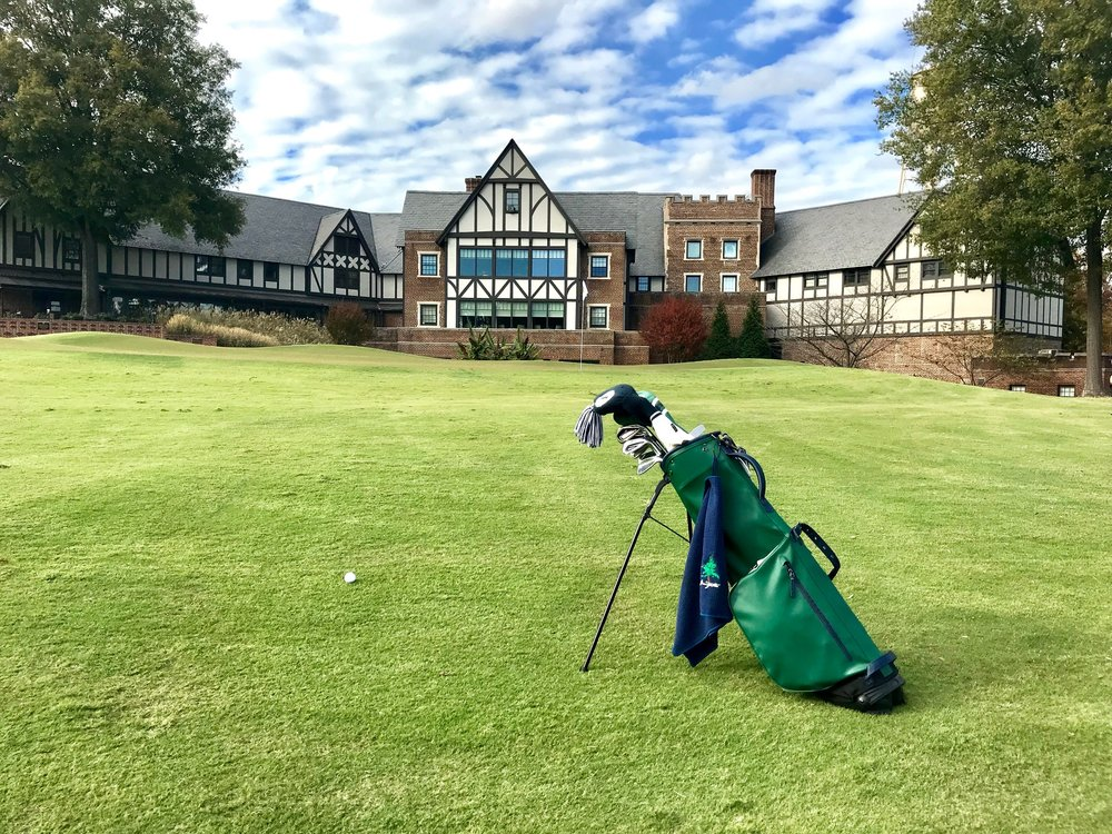 The stately clubhouse that was originally built as a country inn looms behind the ninth green at Sedgefield Country Club.