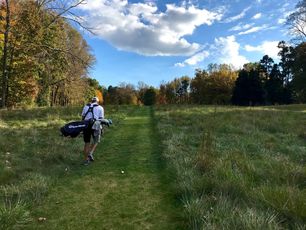 "Sedgefield member Dupont Kirven hauls his bag from the thirteenth tee up to the fairway through one of the walking paths cut as a convenience to walkers. ""It's more enjoyable and I definitely play better when I walk,"" Kirven says."