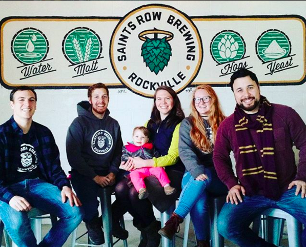 Taproom Staff   Saints Row is a family-owned and operated brewery at its heart. On most nights in the taproom, you'll see Tony's brother Patrick (pictured right) and his  Fiancé  Katelyn (second to the right) greeting you with a smile from behind the bar. You'll recognize CoFounders Lacy and Tony with their one year old daughter Pia in the middle. On the left, you'll see Mike, who also pours beers in the taproom.