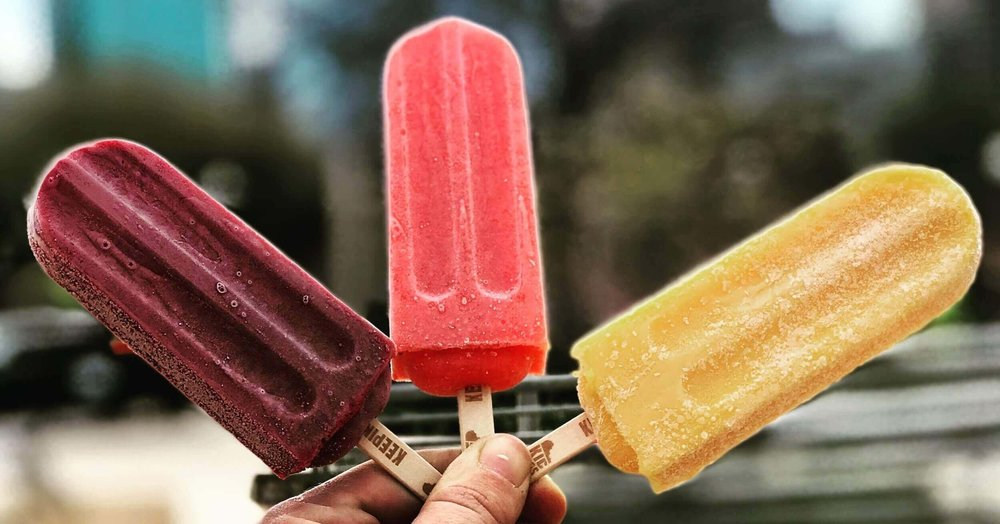 Blackberry Lavender popsicle, Strawberry Lemonade Popsicle, and Mango Coconut Popsicle pictured at a catering event in Houston at Buffalo Bayou Park.