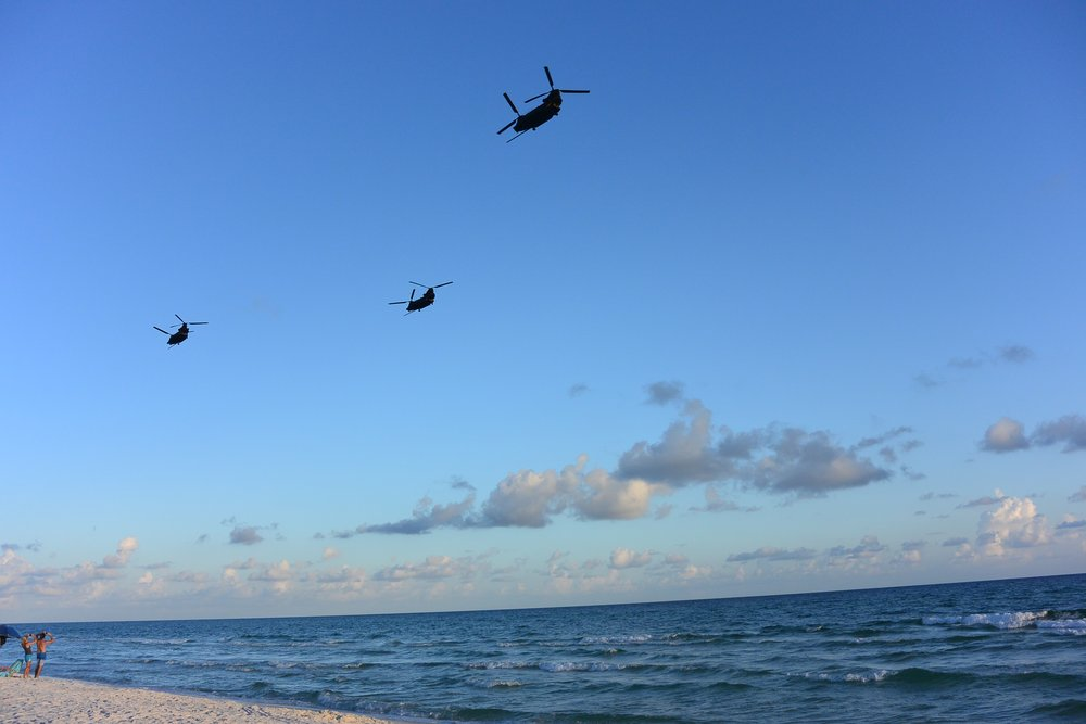 Military helicopters maker their way across the sky at sunset.  Photo by Chic Travels.