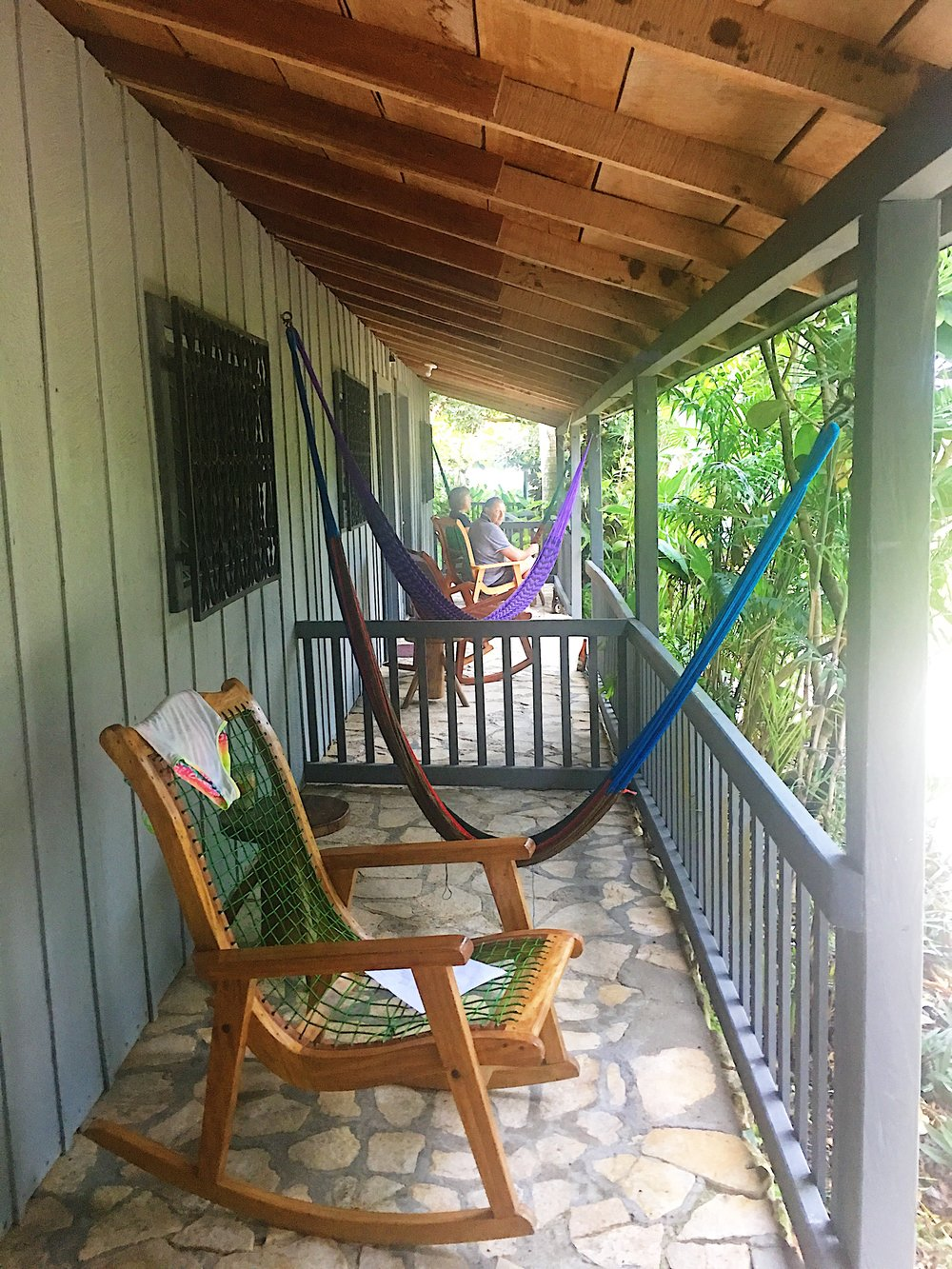 A hammock and rocking chairs sit on the porches outside of the rooms.
