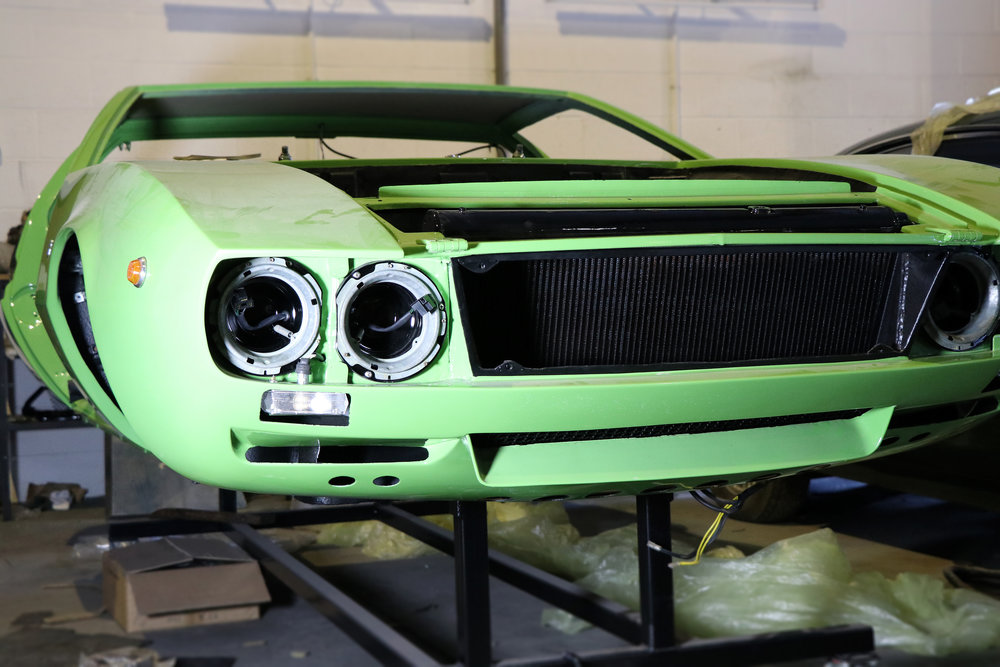 In restoration, De Tomaso Mangusta 1968 in factory apple green, for sale at Three Point Four.