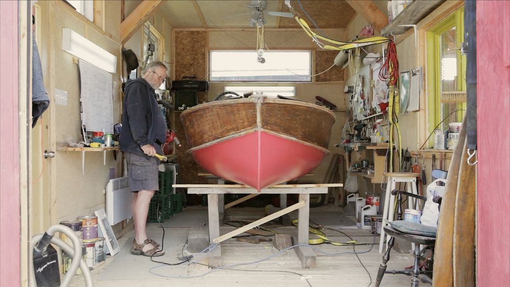 Phil in workshop building boat (wide shot