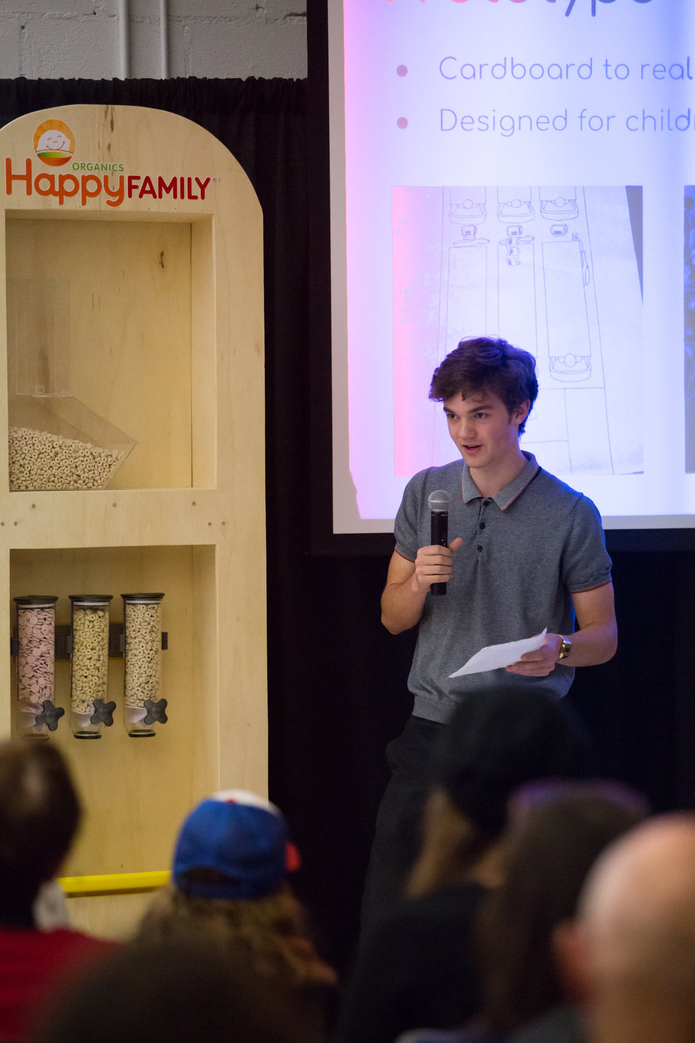A One Stone student presents the prototype for Happy Family Organics bulk food dispensers.
