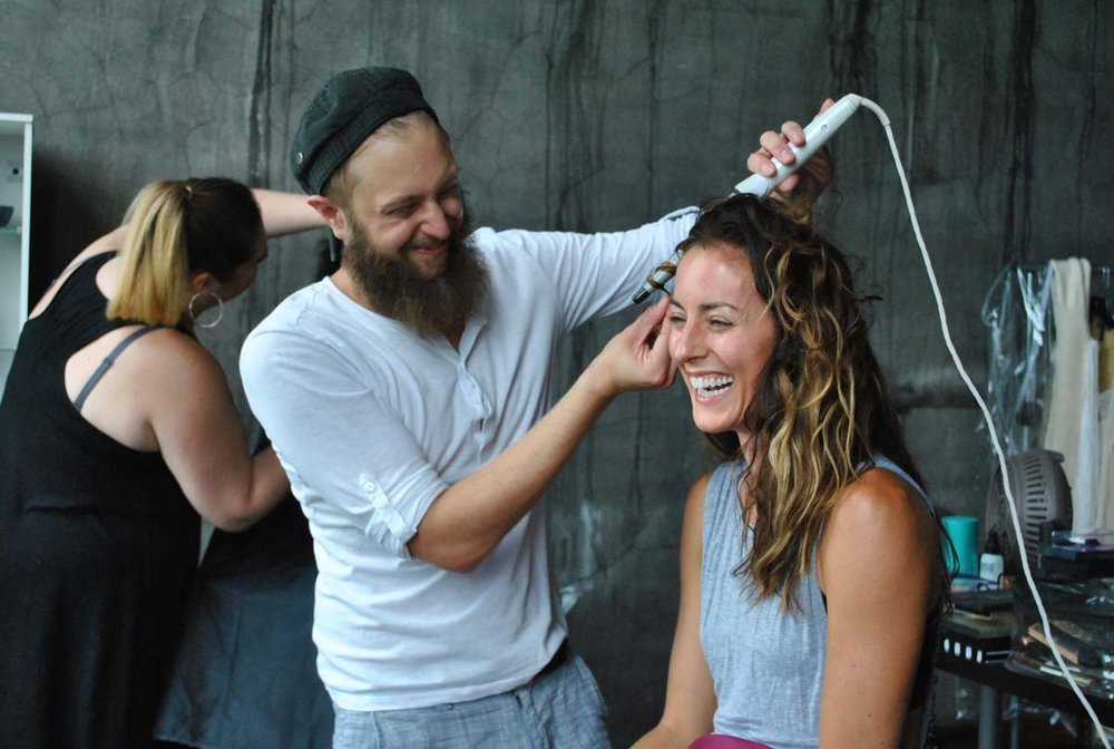 Hair Stylist  Michael Sparto  starts working on dancer  Meredith Hogan 's hair while Makeup Artist  Hannah Dorton  works on a model in the background.