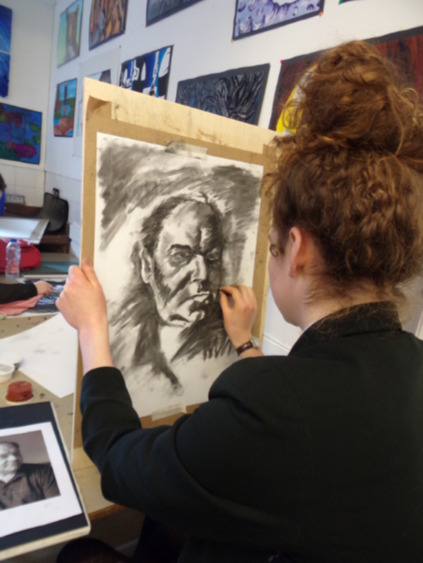 Secondary school student producing a charcoal portrait drawing.