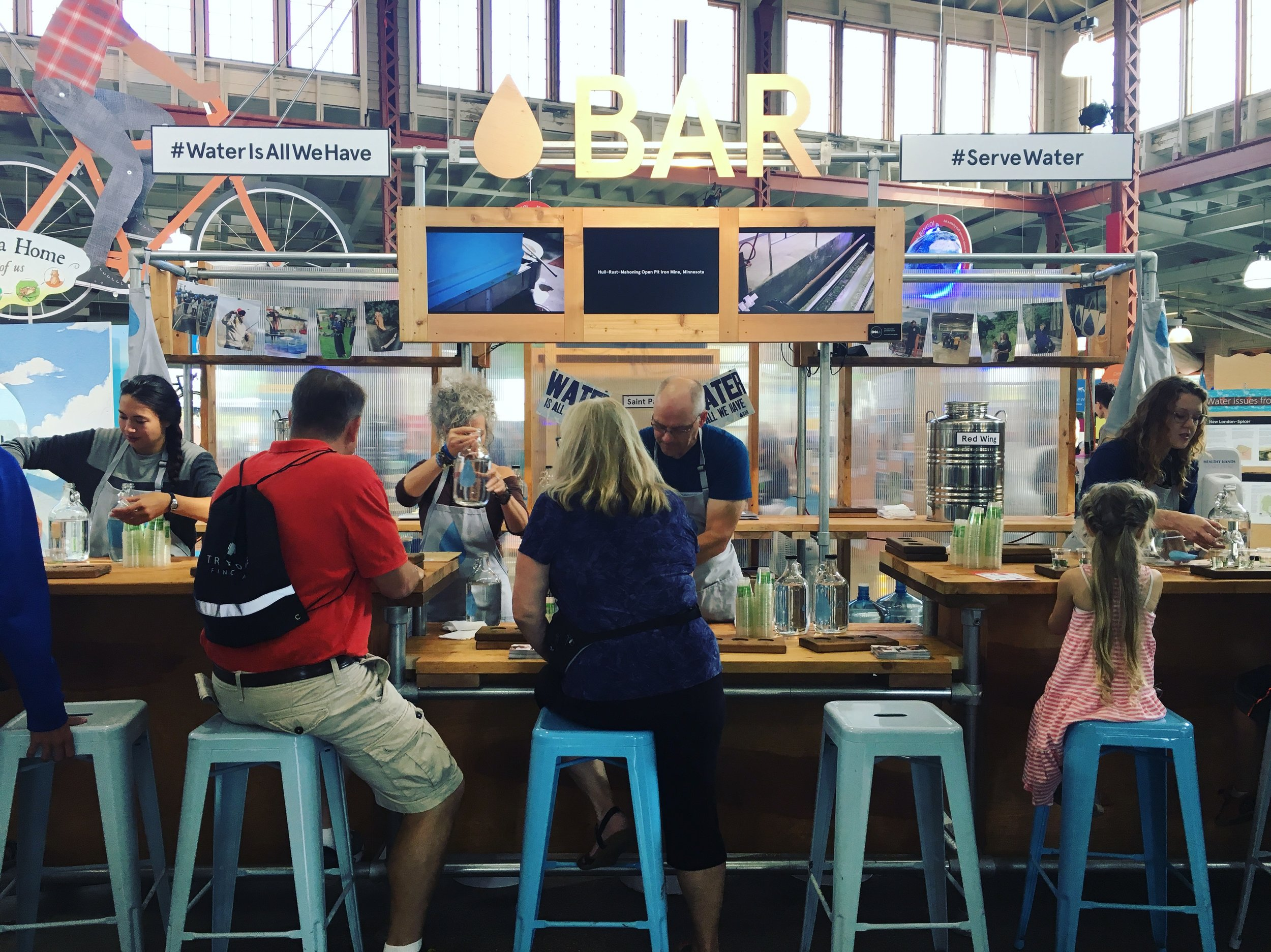 Guests sitting on stools in front of Water Bar, drinking local tap water.