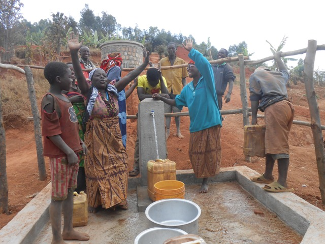 Women at the Karuhaya-Kuntatemwa project celebrate the completion of the first tap stand. Women and children are usually tasked with fetching water for their families and are most impacted by the completion of a water system.