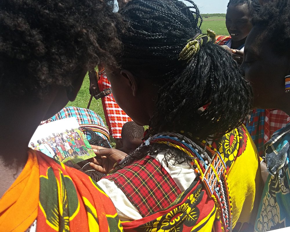 Maasai women looking at picture of themselves.jpg