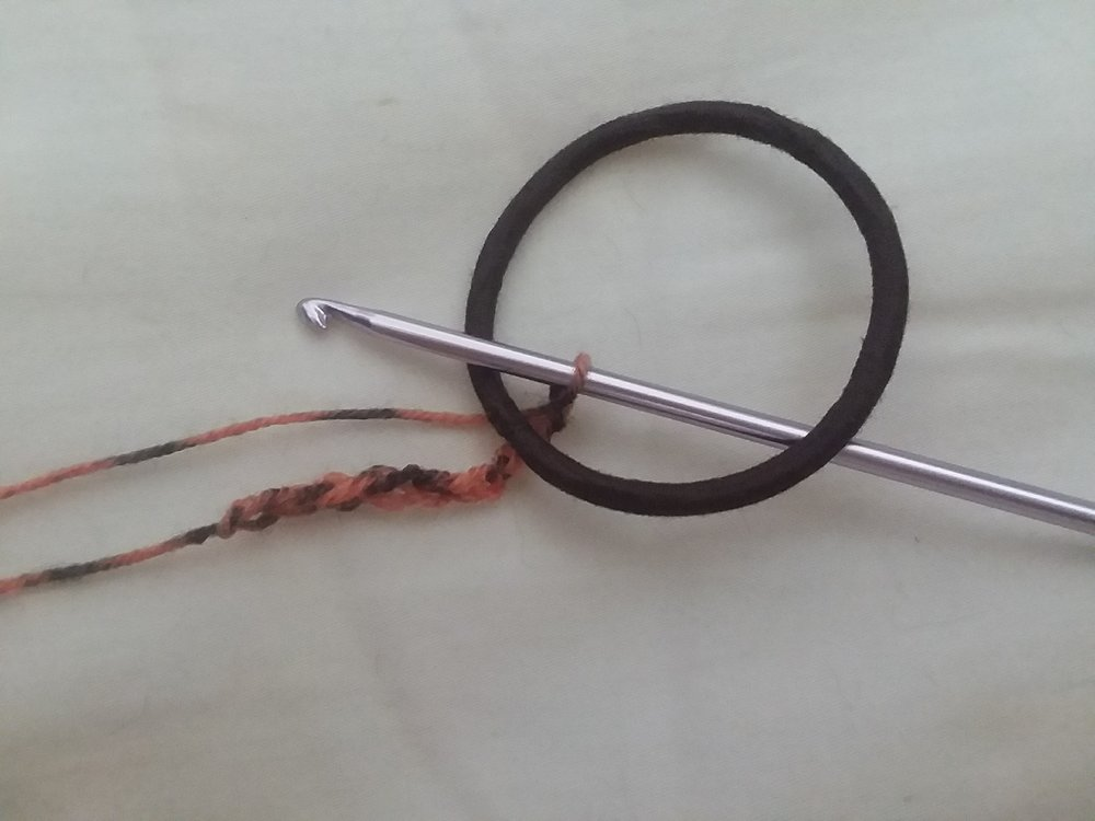 Insert hook with chain into hair tie.
