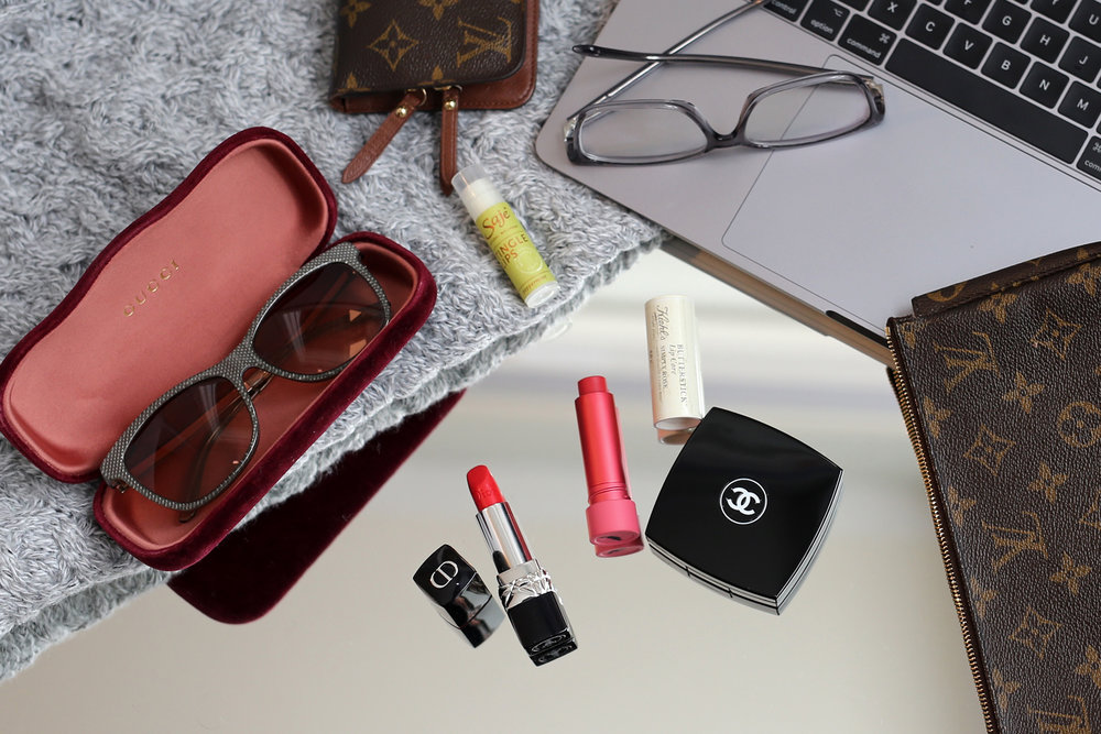 Diana's Louis Vuitton clutch includes Chanel face powder, Dior lipstick in Red Smile, Kiehl's Butterstick Lip Treatment In Simply Rose, Sage Natural Wellness Tingle Mint peppermint lip balm, Gucci sunglasses and eyeglasses, Louis Vuitton wallet and her Macbook Pro, all carried in a nylon Tumi bag for her work commute.