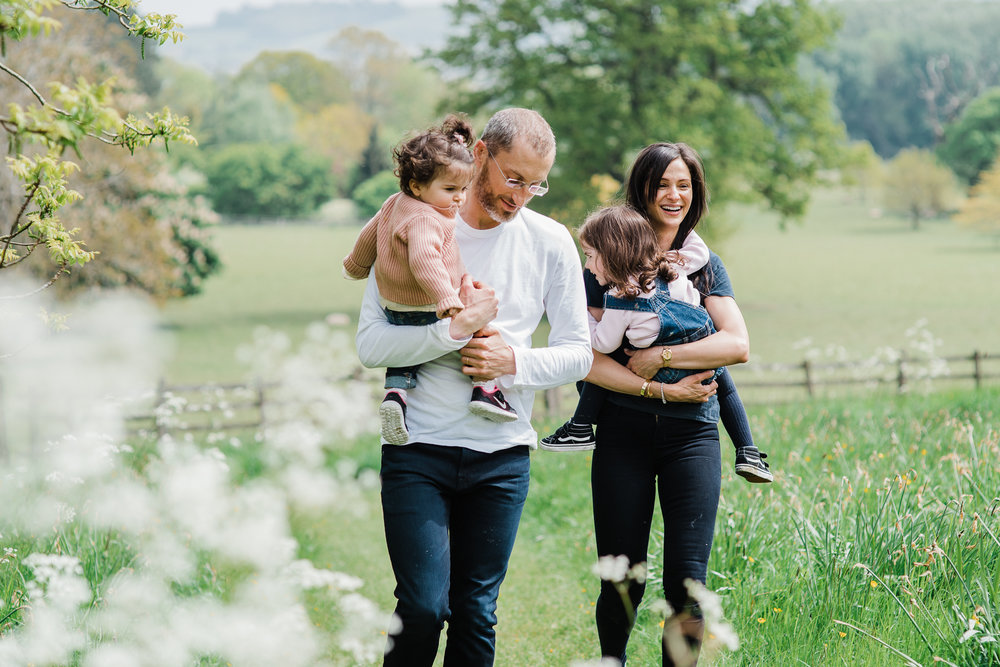 Happy smiling family with two girls walking in summer field