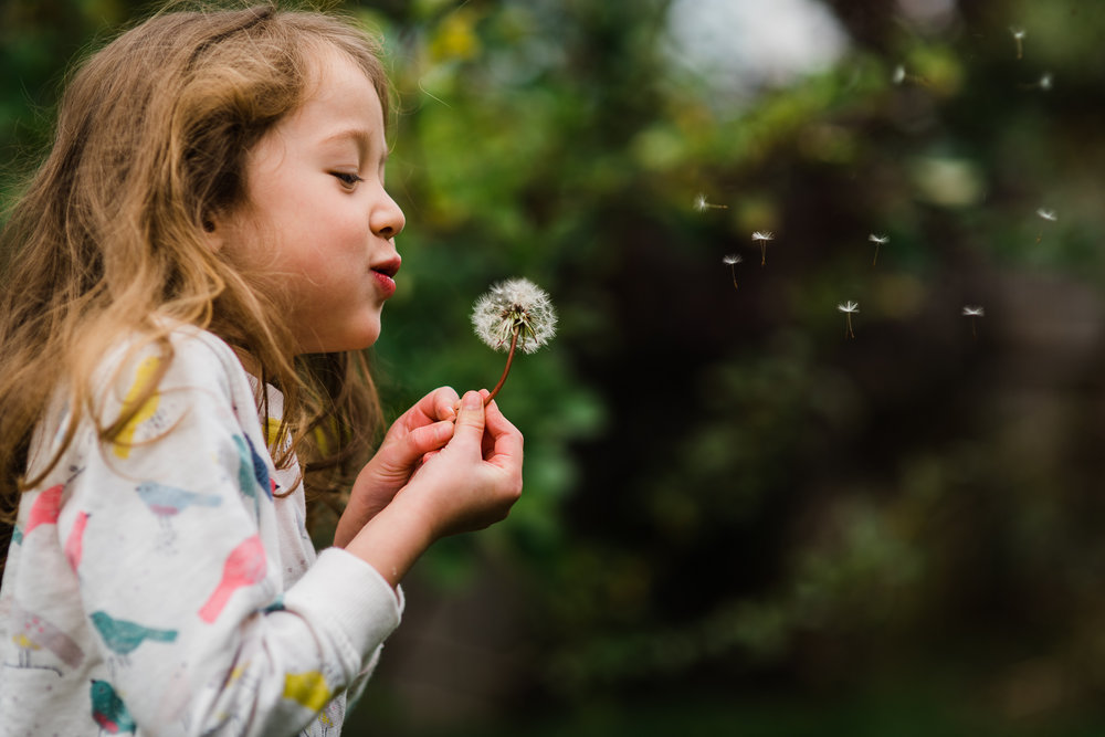 Girl blowing dandelion outside Cheltenham photoshoot.jpg