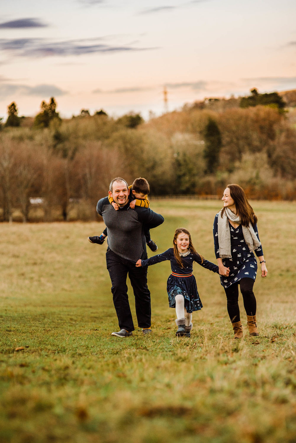 Family running in field- Cotswold Family Photo.jpg