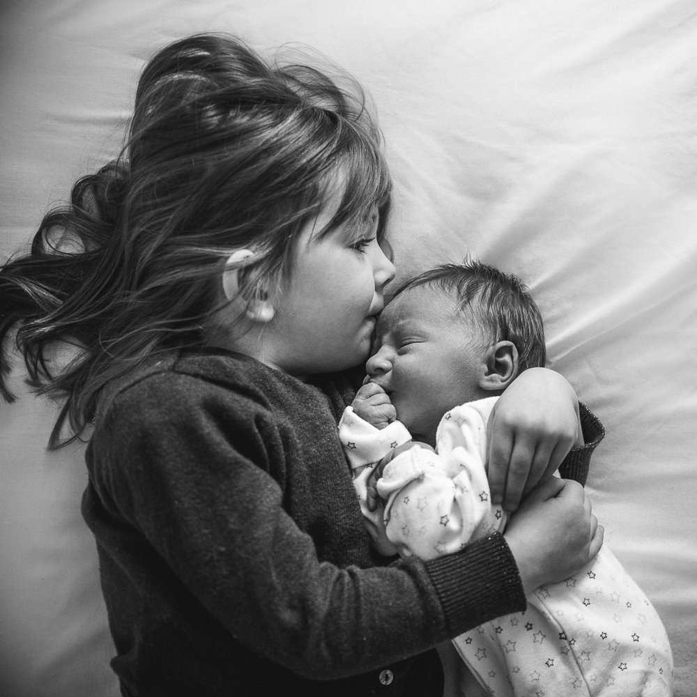 Little girl kissing her baby brother - Cheltenham photograph.jpg