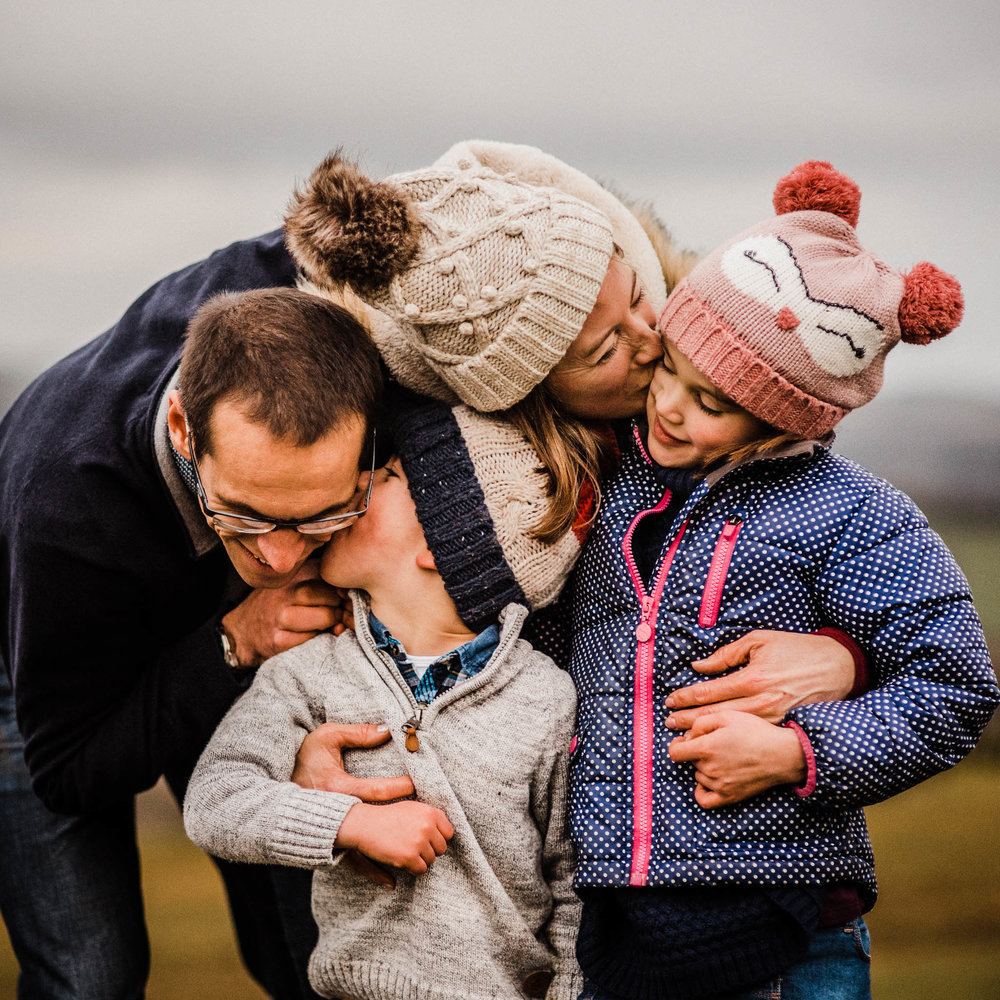 family of four with bobble hats on hill in cheltenham photoshoot