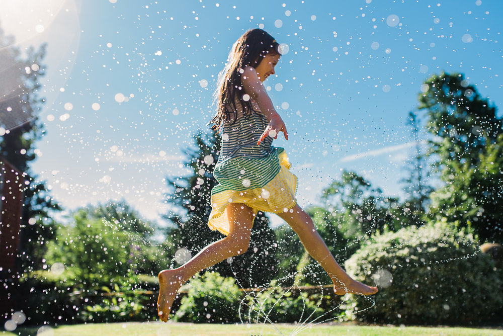 girl jumping through sprinkler at grandparents home