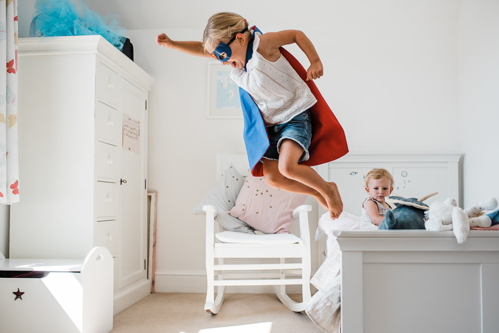 girl in superhero costume jumping off bed at home