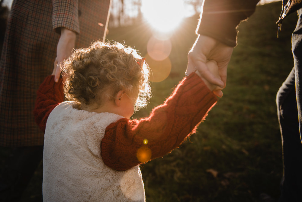 Toddler holding parents hands in sunset