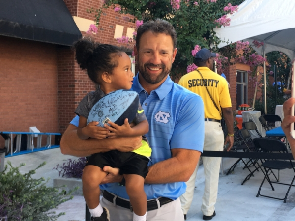 "Head coach Larry Fedora holds a young UNC fan at the ""Meet the Heels"" event on Saturday."