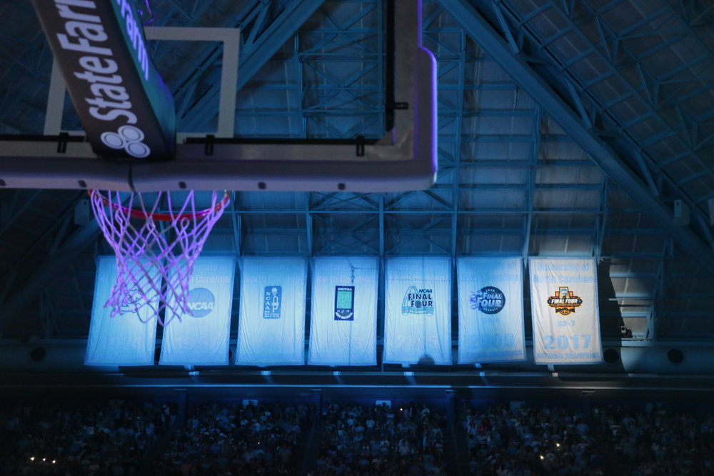 UNC shows off its championship banner at the 2017 edition of Late Night With Roy. The seven banners hang asymetrically, perhaps to provide motivation for UNC | Photo by Gabrielle Palacio