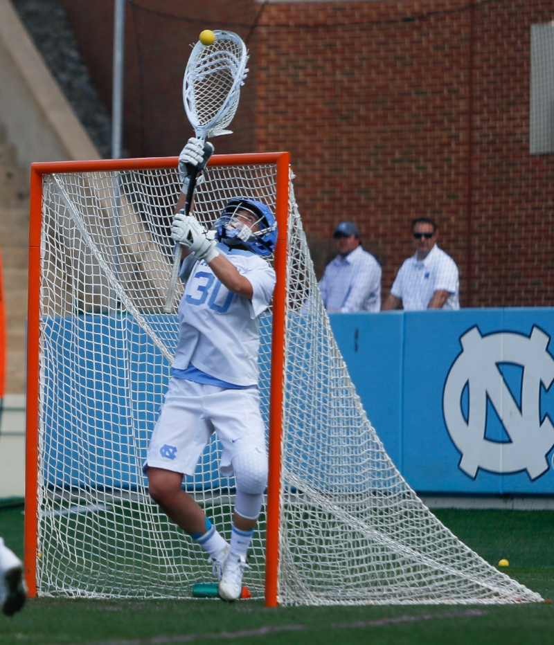 Goalkeeper Taylor Moreno (No. 30) makes a save during the game against Maryland. The redshirt freshman had seven saves off the bench to earn the win between the pipes for the Tar Heels. | Photo by Alex Kormann