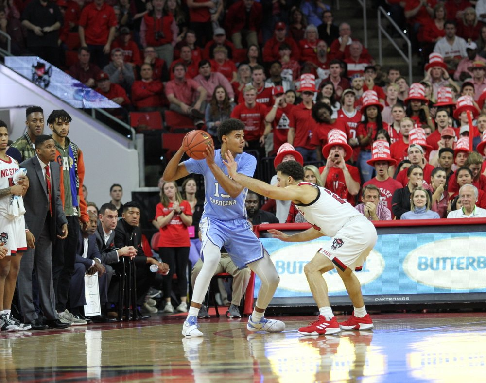 Cameron Johnson looks to make a pass against N.C. State in PNC Arena. The graduate transfer forward was five assists away from a triple-double (15 points, 11 rebounds, five assists) before being forced to leve the game due to cramps.   Photo by Turner Walston.
