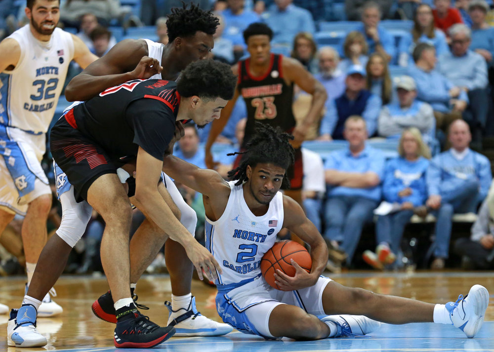 Coby White (2) fights to get off the floor during UNC's loss to Louisville. The freshman point guard struggled throughout the game on Saturday, missing all four of his shots from the field and turning the ball over four times. | Photo by Alex Kormann