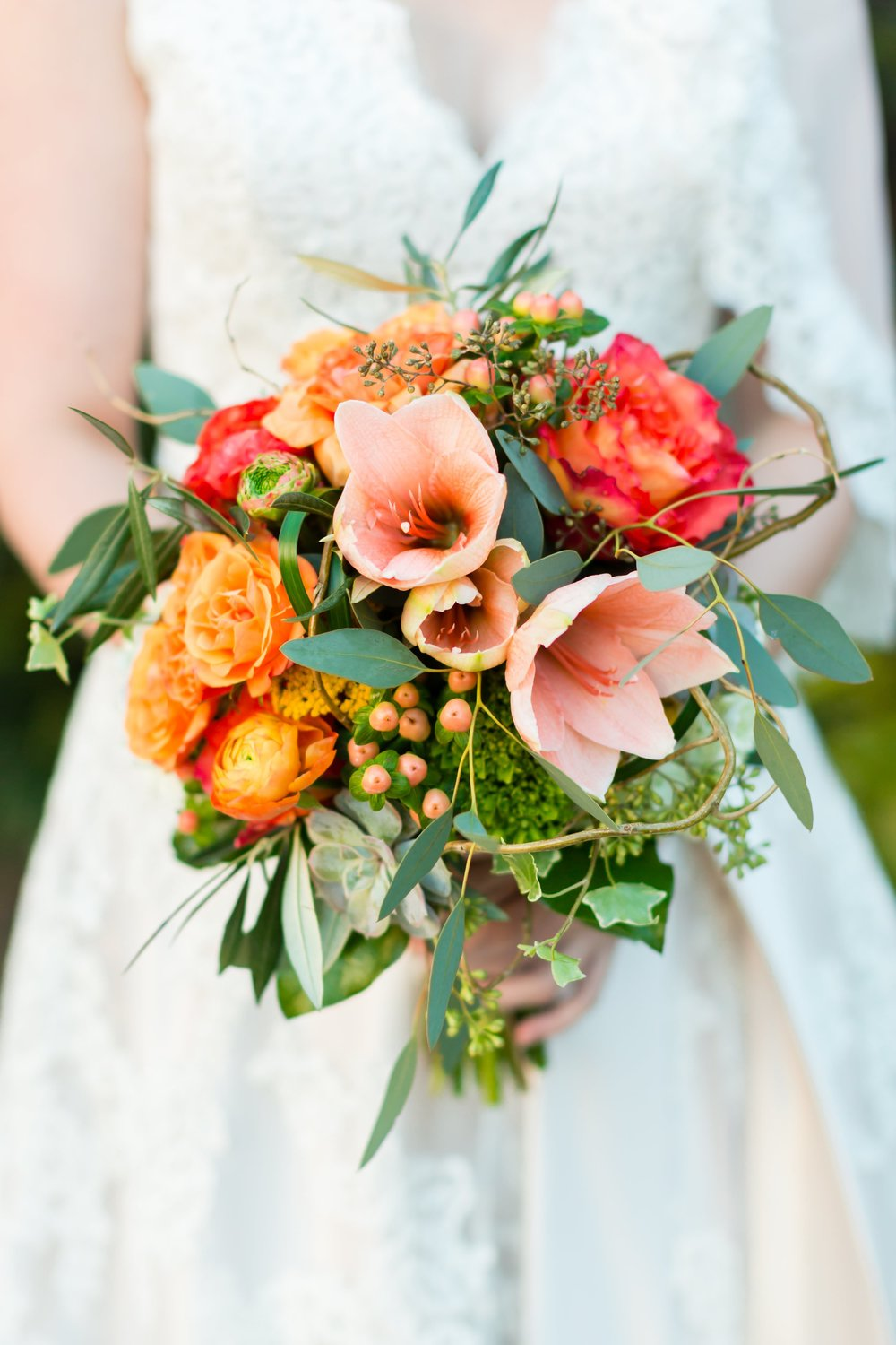 I love how the peach and orange flowers in Corinne's bouquet contrast with the greenery that's mixed into the design. Her bouquet was designed by  Atlanta wedding florist Petals a Florist .