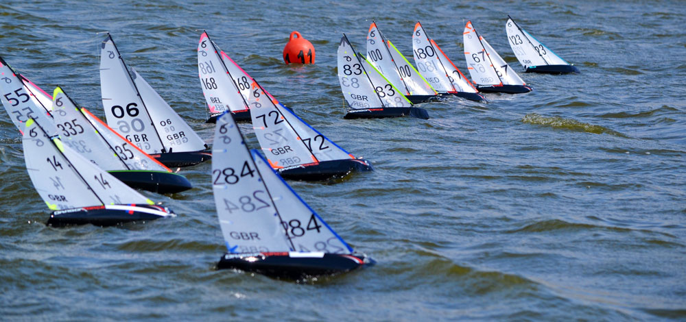 DF65 radio sailboats sailing windward at the start of a regatta.
