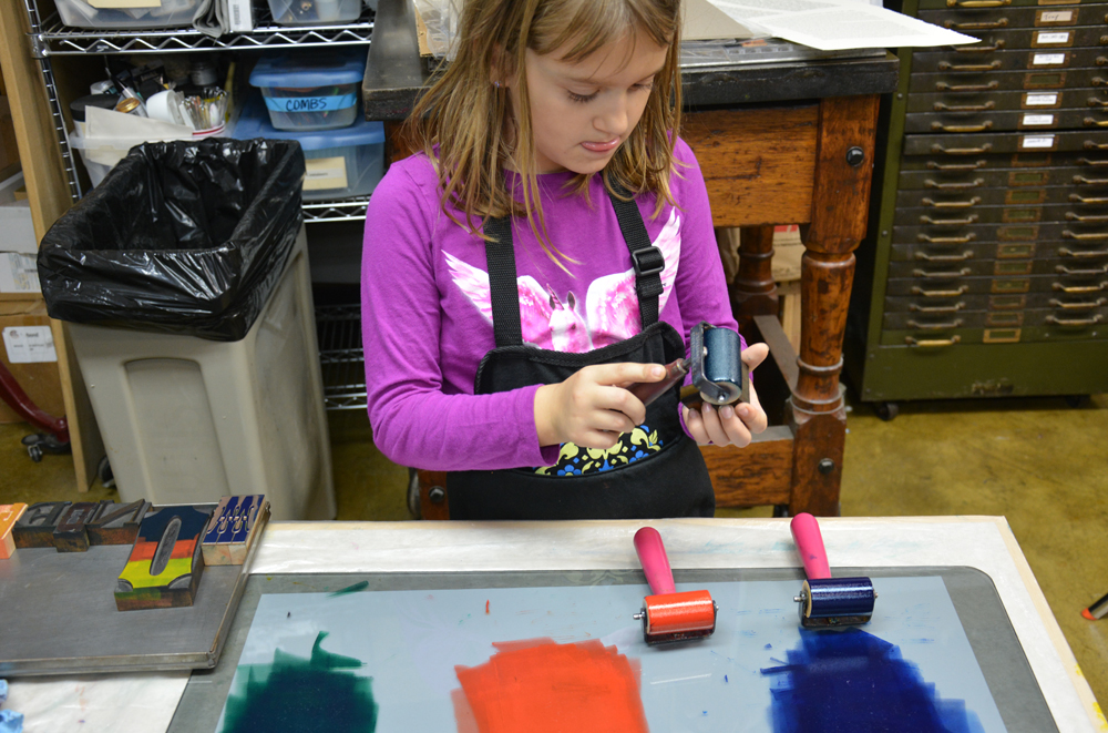 A young participant puts her best Michael Jordan english on her inking-the-type technique.