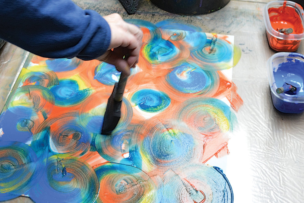 A soft sponge brush is used to apply geometric swirls of colored paste for this high-key design.
